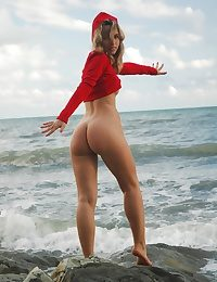 Blonde babe spreading legs on the sea stones